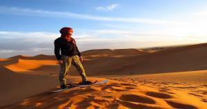 Sandboarding in Merzouga desert, Morocco.